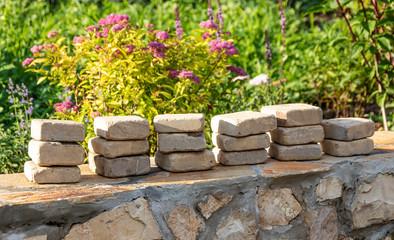 Sandstone paver stacks in the summer garden under reconstruction