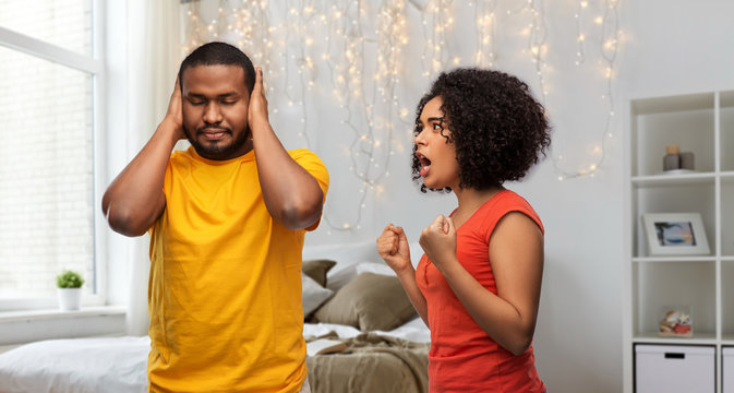 relationships and people concept - unhappy african american couple having argument over home bedroom background