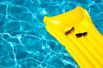 His and hers sunglasses resting on empty yellow inflatable raft floating in bright blue swimming pool