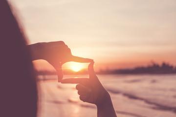 Human hands making a frame sign over sunset sky.