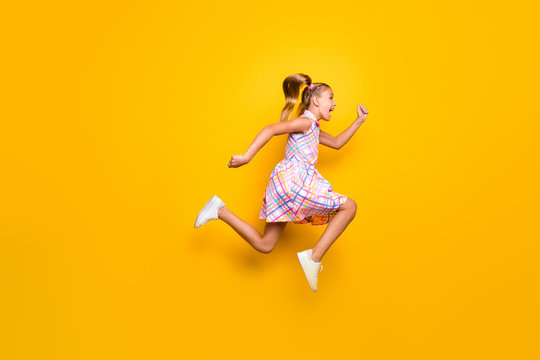 Full body profile side photo of cheerful crazy little girl jump run fast spring time bargains wear trendy style stylish skirt gumshoes isolated bright shine color background