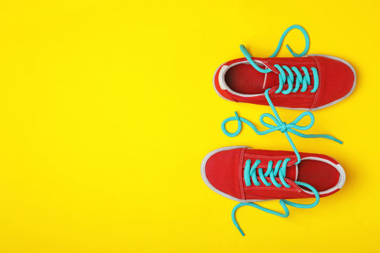 Shoes tied together on yellow background, flat lay with space for text. April Fool's Day