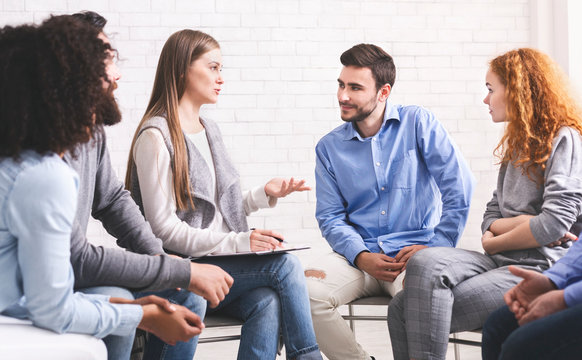 People sitting in circle and listening mentor during group therapy session