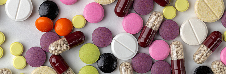 The medicine concept. Multicolored medicines background. Different remedy, pills, capsule, antibiotic and vitamin, panoramic banner.