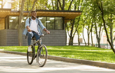 Eco Ride. Happy african american man riding bicycle in city Papier Peint