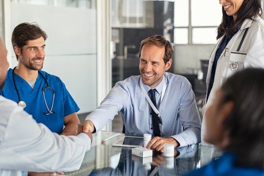 Salesman shaking hands with doctor