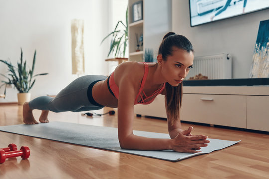 Fit young woman in sports clothing standing in plank position while exercising at home