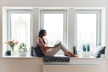 Carefree young woman in cozy pajamas reading a book while resting on the window sill at home Wall mural