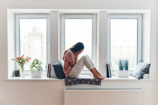 Sad young woman crying about something while sitting on the window sill at home