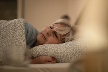 Senior woman sleeping on bed at night.