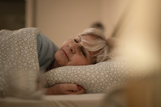 Senior woman sleeping on bed at night.