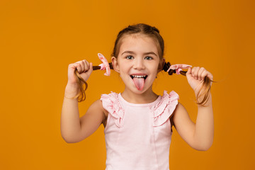 happy funny little child girl showing her tongue on yellow background. facial expression Fototapete