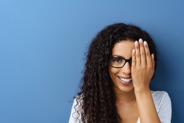 Obraz Happy smiling young woman covering her eye - fototapety do salonu