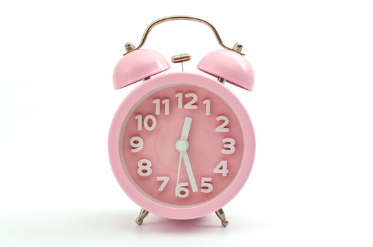 Sleep hygiene, wake up ring and old fashioned clocks concept with pink retro style alarm clock isolated on white background and clipping path cutout