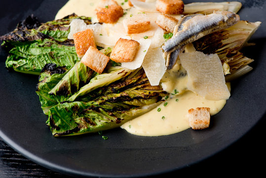 Caesar Salad. Grilled Romaine lettuce leaves topped with classic Caesar salad dressing and garnished with butter garlic croutons shaved parmesan cheese and whole anchovies. Classic American Salad.