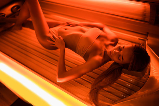 Beautiful young woman tanning skin treatment in modern solarium