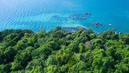 Aerial drone view of rocky shore with turquoise sea water and green trees Fotobehang