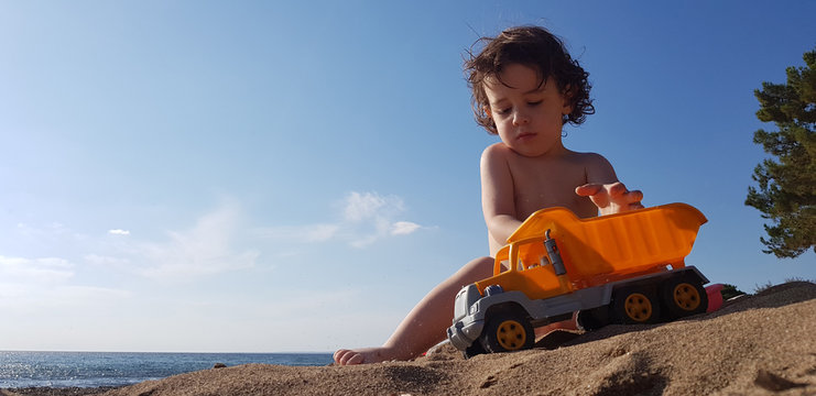 a little boy playing with toy truck on the beach on a hot summer day