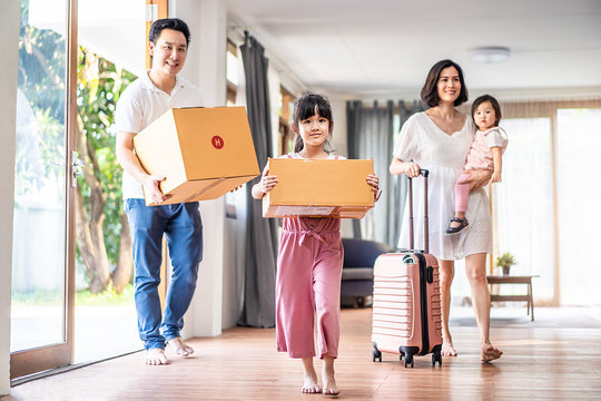Asian big family moving packing boxes and cloth baggage to new house. Mother holding little cute baby girl with suitcase while dad and bigger sister carrying box walking into house with happy, smile.