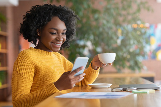 Happy afro woman drinking coffee and using mobile phone
