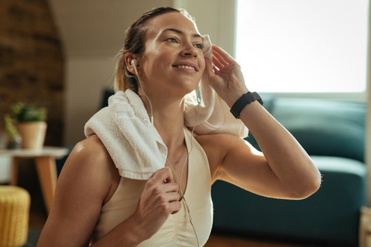 Young happy sportswoman wiping sweat with a towel on a break at home.