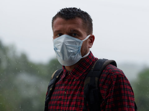 Portrait shot. Male with medical mask and backpack in heavy rain at nature. Rainy weather.