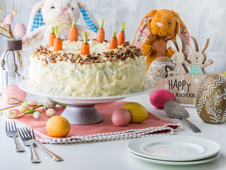 A whole carrot cake on a cake stand with cream cheese frosting surrounded by Easter decorations.