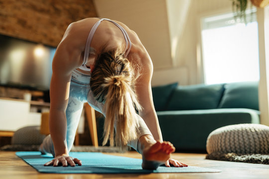 Athletic woman stretching on the floor while practicing at home.