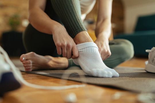 Close-up of athletic woman putting on socks.