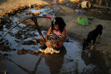 A little girl from the indigenous Wichi community plays with a doll in a puddle of water, in the Salta province