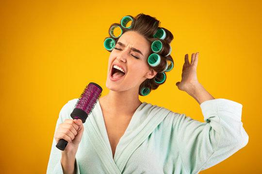 Housewife Singing Holding Hair Brush Like Microphone, Studio Shot