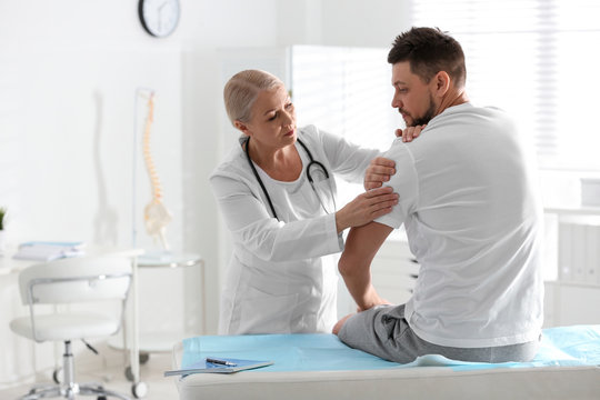 Male orthopedist examining patient's arm in clinic
