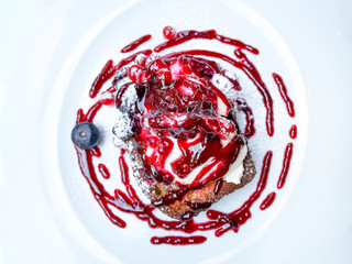 Fototapete - Delicious french toast with cheese cream, blueberries, cranberries and red fruits sauce on top served in white plate for sweet breakfast