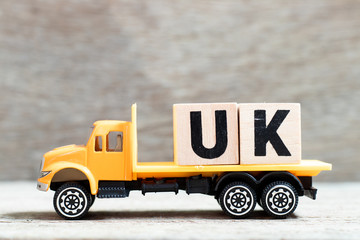 Fototapeta Truck hold letter block in word UK (abbreviation of united kingdom) on wood background obraz