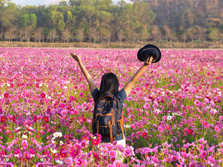 Wall Mural - Back view of freedom tourist woman raises her arm in colorful cosmos flower field