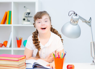 A girl with down syndrome sitting at home at the table reading an open book lying in front of her. Girl with Down Syndrome looking thoughtfully to the side