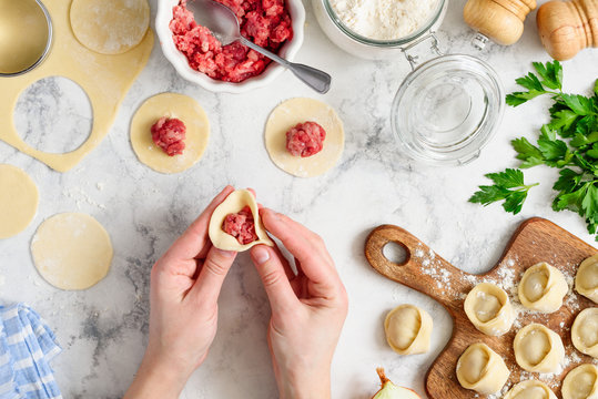 Cooking homemade dumplings or ravioli with meat on marble table. Female hands sculpt dumplings. Traditional russian pelmeni. Culinary concept. Top view