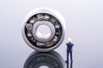 Miniature people : Business man wear blue suit standing in front of ball bearing. Ball bearing place on the other ball bearing. Industrial and business concept Wall mural