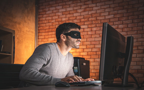 Professional man hacker using keyboard typing bad data into computer online system and stolen personal information.The concept of a criminal, incognito, mystery, secrecy,