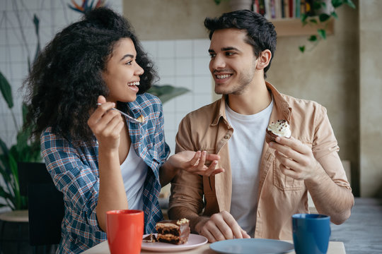 Happy multiracial friends communication together. Young lovely couple laughing, sitting in cafe. Beautiful African American woman and Indian man drinking coffee, eating tasty cake. First date concept