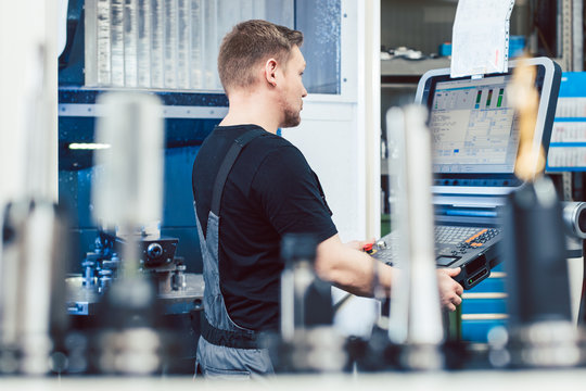 Worker in industrial workshop programming a cnc lathe