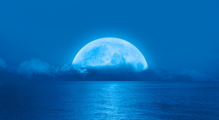 Wall Mural - Night sky with moon in the clouds on the foreground calm sea