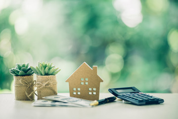 Property investment concept. Wooden house, dollar bill and calculator on table. Pen prepare...
