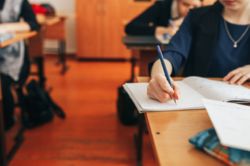 The student writes in a notebook in the classroom, test, exam, writes the text