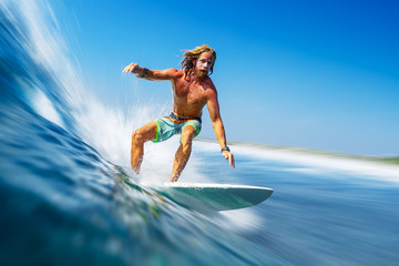 Wall Mural - Young man surfer with long hair surfs the fast and perfect ocean wave in Maldives