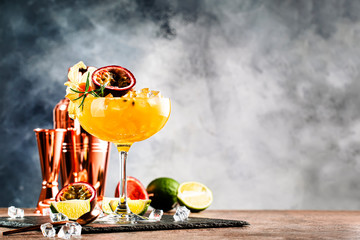 Alcoholic cocktail with fresh passion fruit with rosemary and ice. Gray wood background, bar tools, copy space