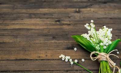 White Spring Flowers. Bouquet of Lily of the valley on a Dark Brown Wooden Background. Greeting for Womens, Mothers Day, Birthday party. Copy space