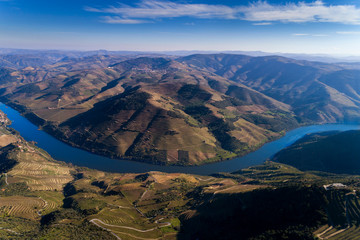 Aerial panoramic drone photograph of the beautiful Douro Valley and the Douro River near the Village of Tua, with the terraced vineayards.