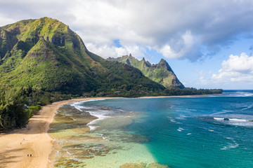 Aerial shot off the coast over Tunnels beach on Hawaiian island of Kauai with Na Pali mountains behind Wall mural