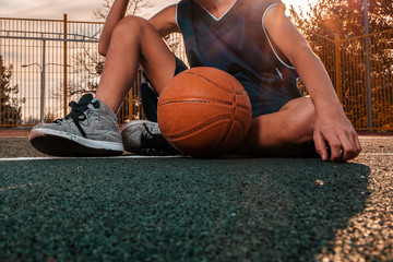 A young teenager in a blue tracksuit poses with a basketball ball sitting on the floor of a sports field. Close up. Sunset in the background. Concept of sport and activity